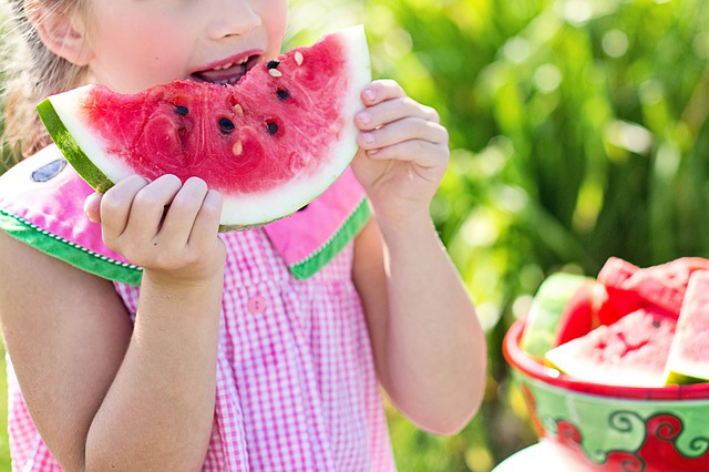 A girl is eating watermelon